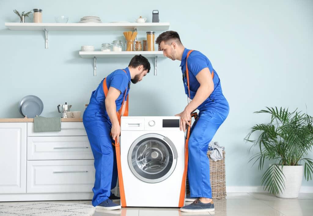 Zwei Männer tragen Waschmaschine